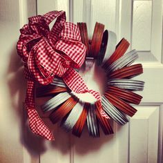 Cute little red and white wreath made from canning jar lids.