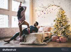 Passionate romantic couple is spending time together before New Year near beautiful Christmas tree at home. Sexy young woman and handsome man are having sex on bed.