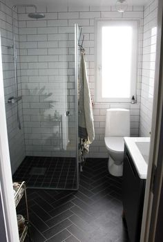 I love everything about this bathroom! The black herringbone floor, the white subway tiles with black grout and the frameless shower doors.