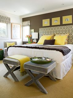 Crisp white walls and trim and hotel-chic bedding serve as striking counterpoints to this bedroom's chocolate-brown wall. A geometric pattern ties the two main colors together, while yellow photo mats and throw pillows introduce a playful splash of color. Two X benches round out the foot of the bed, adding a modern punctuation point and portable seating to the room.