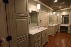 Master bath with double custom vanities, pendant lighting, abundant storage, and stained floors.
