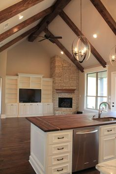 love the openess between the two areas, the entertainment center built-ins and fireplace and the beamed vaulted ceiling