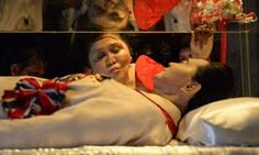 Former Philippine first lady Imelda Marcos kisses the glass case of her late husband Ferdinand Marcos in 2014.