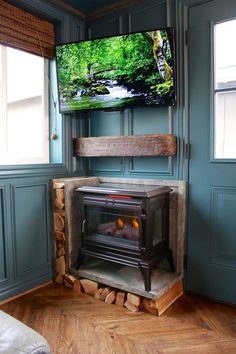 The space feels warm due to the rich blue paneled wall and the electric fireplace, attractively placed under a salvaged oak wood mantle.