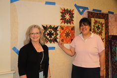 Debbie Caffrey and a student observe completed blocks on a design wall in class.