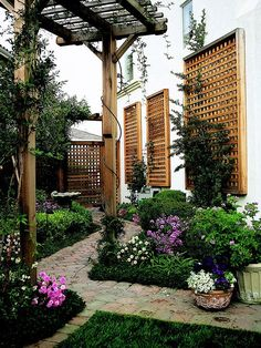 A narrow yard gains depth and interest with trellises, pergola, pavers and lush garden all set on an angle.