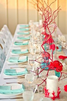"This non-floral centerpiece with tall red coral accents adds ""wow"" factor to a destination wedding or beach wedding."
