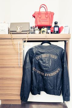"""Inside The Closet of Les Best Amy Patel: """"I am obsessed with outerwear. I take public transportation, and I feel like my commute is my runway [laughs]."""" -- Green YSL purse. black leather jacket and red Celine handbag. 