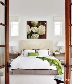 Lucite table lamps, from Wright Now in Chicago, flank the master bedroom's custom parchment- covered headboard.  Style On Picture Lifestyle