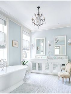 A white bathroom with pale blue walls a mirrored vanity and a herringbone tile floor pattern. Source: