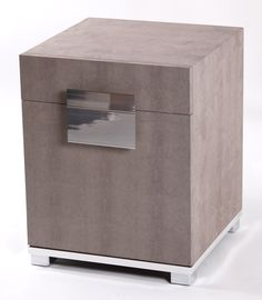 A contemporary leather storage cube shown in iguana lizard grey, with chrome plate trim and feet. The hinged cube is finished internally with faux suede. As with all our pieces, this bedside table has been handmade in England.
