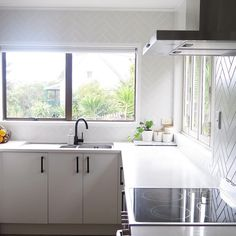 @iamtarryndonaldson on Instagram kitchen  Herringbone full kitchen splashback with black tap ware and handles in an all white space