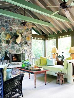 ❤ Get inspired- This dream porch was created during a re-do of a 1930s Lake Michigan cabin. The screen porch was enlarged to 20 x 20 feet for entertaining, and the porch's new 18-foot-tall stone fireplace includes a raised hearth that's wide enough for sitting.    If you like the look, adapt parts of it to fit your budget: the pretty green beams, a comfy sofa, even just an unusual end table.