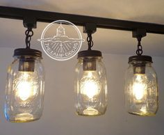 Super cool Mason Jar Track Lighting system showcasing three authentic mason jars pendant lights ready to renovate your current boring light fixtures. Mason Jar Pendant Light, Mason Jar Light Fixture, Mason Jar Chandelier, Mason Jar Lighting, Chandelier Fan, Chandeliers, Pantry Lighting, Bottle Chandelier, Track Lighting Fixtures