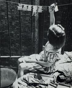 Lucy Ashjian     Child Hanging Baby Clothes on Clothesline,  New York City     c.1935