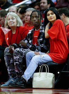 Bonding: Travis Scott has been telling friends he and Kylie Jenner - pictured at a Houston Rockets game on April 25 - are 'the real deal' according to a Wednesday report from Us Weekly