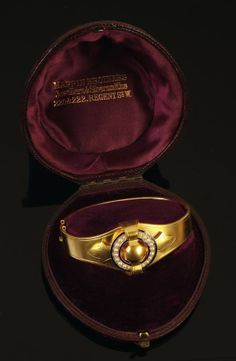 A late Victorian gold, half pearl and enamel bangle, circa 1880, the shaped top applied with a half pearl circlet in a blue enamel surround, on a bloomed gold tapering hinged bangle, inner diameter 5.3cm widest, in a Mappin Brothers red leather bound velvet fitted horseshoe case.