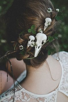 Skulls pinned in her hair; she is death and she is life.