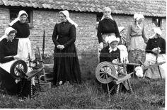 Tafereeltje in Veluwse klederdracht tijdens het spinnen van vacht tot wol bij de schaapskooi aan de verlengde Arnhemseweg in Ede. De derde staande vrouw van links is mej. IJsseldijk. 1964 #Gelderland #Veluwe