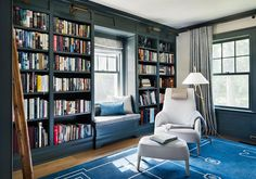 Dark blue paneled den boasts a white chair with matching ottoman placed atop a blue rug illuminated by a brass floor lamp.