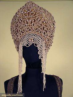 "3-piece, sarafan/jumper-style dress of dull olive cotton brocade, trimmed w/ gold gimp & pearls, sequins & large jewels, B 38"", L 55""-57"" (gold lace on shoulders damaged); fur trimmed burgundy & gold lame brocade jacket, (ivory silk lining shredded), L 22"", Slv L 29.5""; kokochnik/headress of rhinestones & pearls encrusted on gold braid lace, pearl fringes frame face, gold lame (damaged) lining & crown,"