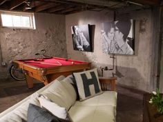 Exposed concrete walls give this basement hangout an industrial vibe. The space is made more inviting with a pool table, large black and white portraits and a white couch with bold lettered throw pillows.