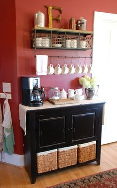To achieve this look, simply find a socially central wall or nook, install some shelving and a cabinet, then set up the electronics and accessories. Have fun with this project and go with your own decor style, like how graphic designer-artist-blogger Carrie from the Vintage Wren did with a beautiful old buffet and this funky, vintage-styled shelving and storage bins. She then placed personal items thoughtfully to enliven the space, like collectable coffee pots and an expressive family initial...