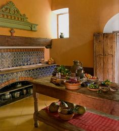 hacienda kitchen in mexico. tiled counter and oven, wooden island, bright walls. Inspirational kitchen decor and design.