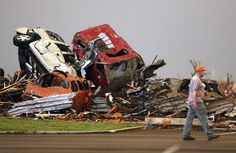 A man walks past destroyed vehicles in the parking lot of the Joplin Regional Medical Center. (AP Photo/Mark Schiefelbein) Joplin Tornado May 22, 2011