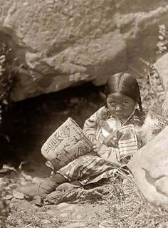 Old photo of a Chinook Child in Springtime. It was made in 1910 by Edward S. The photo documents a young Chinook girl seated on the ground holding a basket, in front of a spring, with large rocks around her. Native American Children, Native American Beauty, Native American Photos, Native American History, Native American Indians, Native Indian, Native Art, Indian Tribes, First Nations