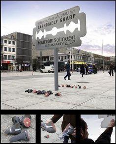 Valla publicitaria (anuncia filo de una marca de cuchilas). En el suelo: palomas que se han cortado por la mitad al posarse en la valla