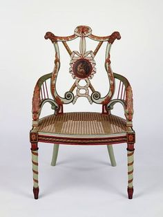 Armchair, London, England ca. 1780-85. Carved and painted beech, with caned seat. This chair is part of a larger suite that formerly furnished the Music Room at Woodhall Park, Hertfordshire. It is appropriately decorated with emblems of music - the back carved in the form of a lyre with two pipes crossed in the centre, the round medallions painted with female musicians. The arms, carved as dolphins, represent the dolphin that saved the life of the Greek poet and musician Arion.