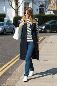 Mulher morena andando nas ruas de Londres vestindo blusa de manga comprida listrada, calça jeans de modelagem reta, colete longo azul marinho, tênis branco, bolsa branca e óculos escuros