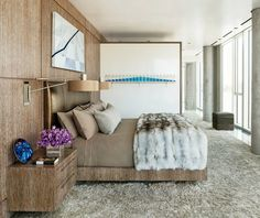 Modern bedroom decorating ideas | Randy Kemper and Tony Ingrao designed the master bedroom cerused-oak wall paneling with integrated bed and nightstands; the swing-arm sconces are by Lorin Marsh, and the shag carpet is by Darius | #masterbedroom #bedroomideas #bedroomdecor