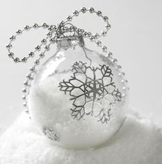 Snowy Rebirth~ Remove the ornament's metal top. Fill the ornament about one-half to two-thirds with artificial snow, glitter, Epsom salts, or sugar. Put top back on. Adhere silvery snowflake decals designed for scrapbooking to the ornament. Loop a string of crafts store beads or an office supply ball chain through the top; tie the beads into a bow