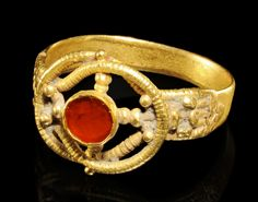 ROMAN GOLD FINGER RING WITH BEZEL-SET RED GLASS ROUNDEL  						  						Within a Herakles knot enhanced with gold beading in cruciform.  						  						4th-5th Century AD