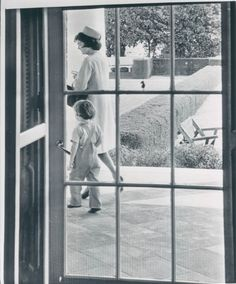 March 16th, 1961 – Caroline tags along with her mother, First Lady Jacqueline Kennedy, as Mrs. Kennedy walks past the Chief Executive's White House office door. The First Lady is on her way to join the President and accompany him to the State Department to attend the centennial celebration of Italian Unification.
