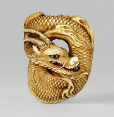 A large and impressive stained ivory netsuke of a coiled dragon. Mid-19th century