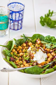 Marvelous Moroccan Chickpea Salad | Chickpeas, also known as garbanzo beans, are marinated in spices, preserved lemon, garlic and olive oil for several hours before being served on a bed of spinach leaves with Greek yogurt, pistachios, and dried cranberries