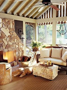 A large stone fireplace is the centerpiece to this screened porch that sits in a wood cabin along Lake Michigan. Fire logs are nestled in a silver drink tub next to a slipcovered ottoman with a floral and fruity pattern. Vaulted wooden ceiling beams are juxtaposed with a striped awning and a shapely light fixture. (Photo: Matthew Gilson)