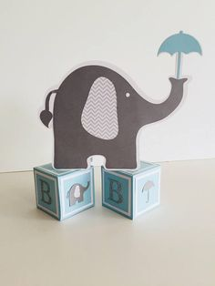Darling elephant and umbrella table decorations that can be changed to match your colors for your next elephant baby shower. Cute elephant holding an umbrella on two alphabet blocks. Comes as once piece, ready to be placed on the table, and the focus can then move on from decorating to