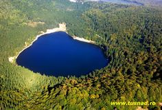 Lake Sfânta Ana is the only crater lake in Romania located in the volcanic crater of the volcano named Ciomatu Mare of the Eastern Carpathians, near Tușnad in the Natural Reserve of Mohoș, Harghita County, Romania. Turism Romania, Visit Romania, Romanian Flag, Fairytale Castle, Crater Lake, Tourist Places, Bucharest, Places To See, Europe