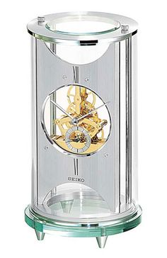 """The Seiko is in a cylindrical silvertone metal and glass case with an exposed skeleton Movement. Silvertone chapter ring with a sub-Second Dial. One """"AA"""" Battery Included. Size: H 9 W D Contemporary Mantel Clocks, Seiko, Metal, Glass, Skeleton, Ring, Rings, Drinkware, Modern Mantel Clocks"""