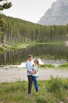 Summer Engagement Session - Red Lodge - Mountains - Trees - Lake - Water - Grass - Embrace - Sunset - Fiance - Engaged Couple - Gray Pants - Blue Shirt - Green Shirt - Jeans - Holding - Montana Wedding Photographer - Sara Nagel Photography Engagement Couple, Engagement Session, Engagement Photos, Red Lodge Mountain, Montana Wedding, Lake Water, How To Pose, Gray Pants, Green Shirt