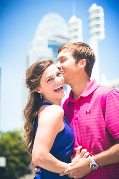 Engagement photos downtown Cincinnati in front of the Red's stadium. Cute couple poses for engagement sessions and photography outdoors. Laughing and big smiles. Blue and pink outfits