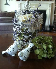 Touch of spring- flower tops (hydrangeas) in cage with a decorative beading. Add birds & butterfly