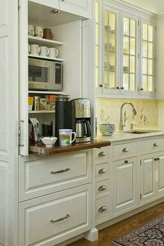 Coffee and microwave hidden behind doors with a pullout shelf below