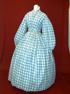 Check plaid sheer cotton; high pleated bodice, band collar, bodice closure in lining, bishop sleeves gathered into band, pleated skirt. GRACEFUL LADY