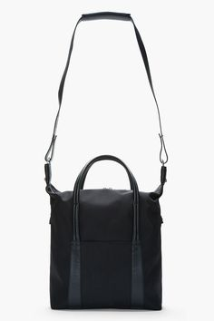 "MAISON MARTIN MARGIELA - Black textile and leather tall tote Structured nylon tote in black. Tonal leather trim throughout. Silver-tone hardware. Two-way zip closure at main compartment. Leather carry handles. Removable adjustable shoulder strap with press-stud fixtures at base. Welt pocket at exterior face. Patch pockets and zippered welt pocket at interior. Approx. 14"" length, 5"" width, 15"" height. Shell: 100% nylon. Trim: 100% calf leather. Lining: 100% cotton. Made in Italy. $995 CAD"