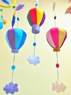 Móbile de balão colorido com nuvens super fofo em feltro, para dar uma sensação de estar voando e sonhando alto! Perfeito para pendurar numa varanda, numa janela e também para decorar o quarto de uma criança. Inspirador e divertido, esse móbile vai te levar às alturas!